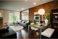 A brick wall and rustic wood floors pair with contemporary furnishings. The Aster model from the Neighborhoods of EYA at Mosaic District. Newly built townhomes in Fairfax, Virginia.