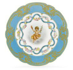 A RUSSIAN PORCELAIN DESSERT PLATE FROM THE ALEXANDRINSKY TURQUOISE SERVICE, IMPERIAL PORCELAIN MANUFACTORY, ST. PETERSBURG, PERIOD OF NICHOLAS II (1894-1917), 1899 scalloped, the center with a putto with thyrsos and mask bordered by interwoven floral bands and ribbons, the border with ciselé gilt wreaths and scrolls against a turquoise ground, with green Imperial cypher of Nicholas II