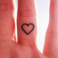 Pequeño tatuaje en el interior del dedo anular de un corazón.