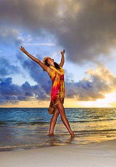 Hawaii, Oahu, Lanikai, Beautiful Hawaiian woman dancing hula on ocean shoreline.
