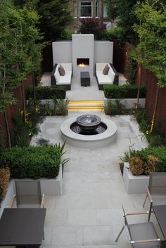 Cacading David Harber water Chalice w/i a pool.  Pleached Hornbeams & honeysuckle. Putney Garden Design Project designed by Simon Tomas, installed by Landscaping Solutions - Putney Project