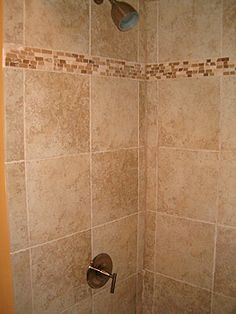 i like this idea of breaking up shower tile   Bathroom: tiled shower with mosaic pattern