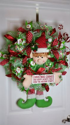 This deco mesh Christmas wreath features an elf with a sign that says, CHRISTMAS COOKIES AND HAPPY HEARTS THIS IS HOW THE HOLIDAY STARTS. It also includes decorative candy canes and peppermints, and wired ribbon. The wreath is red, green, and white.  W 23 H 31 with legs