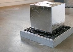Stainless Steel Cube - Water disappears into a shallow bed of black rocks, beneath this mirror-polished stainless steel cube. This stainless steel cube design can be made in most any dimension for all indoor or outdoor spaces, and is particularly appropriate for modern spaces that would benefit from a highly reflective surface. Our team is eager to create a modern feature per your specifications and preferences. Type: water sculpture for private residence. LA. By Water Studio.