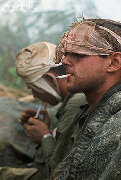 04 Apr 1968, Near Khe Sanh, South Vietnam --- 4/4/1968-Near Khe Sanh, South Vietnam- First cavalry men, many with head wounds, wait to be evacuated from a hilltop along route #9, during their advance toward Khe Sanh. They are shown close-up, smoking.