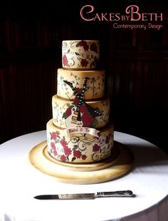 Love Rocks - Guitar and tattoo-themed wedding cake. Hand painted rose and vine tattoo details, vintage colour effect and bride and groom crossed guitars.