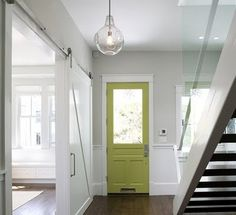 Modernized entryway with glass pendant and sliding barn door.