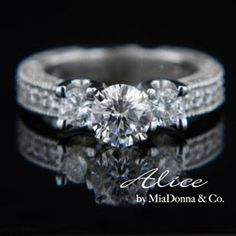 MiaDonna- The Alice is a classically antique styled Engagement Ring or Anniversary Ring covered in stones with great detailing to the metal. Available in your choice MiaDonna Hybrid Diamond center stone shape and size with 2 x 0.25ct or 2 x 0.75ct MiaDonna Diamond Hybrid side stones. The Alice also has approximately 0.75 total carats of natural accenting diamonds on the band.