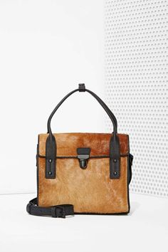 Looking for the ultimate pony hair bag? This satchel by IIIBeCa has a a tuck/lock closure at front foldover flap, top handle, matte black hardware, and an adjustable buckle closure at shoulder strap.