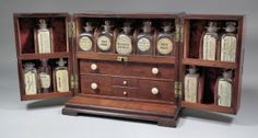 A late Georgian mahogany apothecary's box, the front opening to reveal drawers containing scales, glass cupping cups and pestle and mortar, and thirteen glass ointment jars with labels (four missing), and a secret sliding compartment to back containing poison bottles, 12ins x 7ins x 10.75ins high
