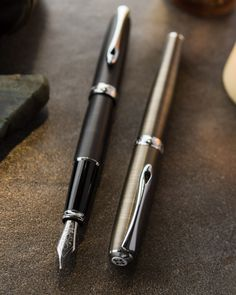 This Diplomat Excellence Brass and Iron fountain pens feature a champagne or charcoal grey-like color obtained by metal oxidation, with chrome trim. Expensive Pens, Goulet Pens Company, Black Background Wallpaper, Pen Collection, Stationery Pens, Fountain Pen Ink, Penmanship, Writing Instruments, Champagne