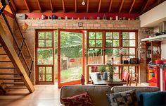 A iluminação e a ventilação naturais entram em abundância graças às grandes aberturas com vidro criadas pela arquiteta Kita Flótido. A porta de entrada pivotante fica na fachada repleta de janelões, que funcionam como balcão de apoio para a cozinha