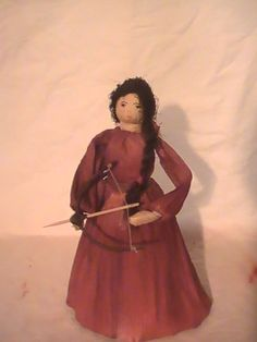 Indian Maiden holding a bow and arrow with paboose on her back. Created from corn shucks with corn silk hair and hand drawn face. $25.00