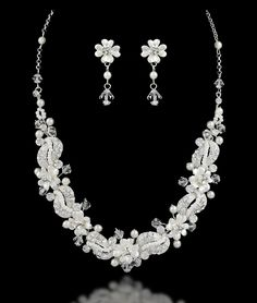 This wedding necklace design has a lot of sparkle! Waves of ivory seed beads and rhinestones connect silver frosted flowers accented with swarovski crystals and ivory pearls.