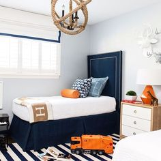 Such a fun color palette for a little boys room.  The orange pops off of that navy so well! Love the rope chandelier and striped rug.