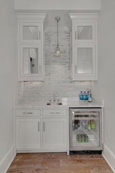 White cottage butler's pantry features mirrored upper cabinets and white lower cabinets fitted ...