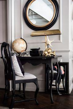 Snygg, rund spegel med svart- och guldfärgad träram