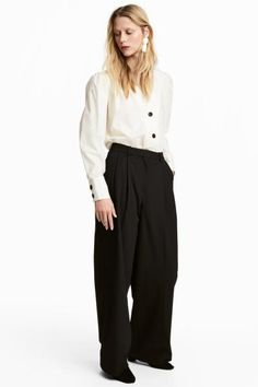 Wide suit trousers in sturdy twill with pleats at the top, a concealed hook-and-eye fastener and zip fly. Side pockets, welt back pockets and legs with crea