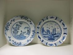 A mid 18th century Delft blue and white dish, possibly London and another possibly Liverpool, the centre of the first painted with a peacock perched on an island by a rock within four sprays of flowers on the rim, 34cm (13.25 in), the second with ships sailing by a tower at the mouth of an estuary, 34cm (13.5 in ) diameter