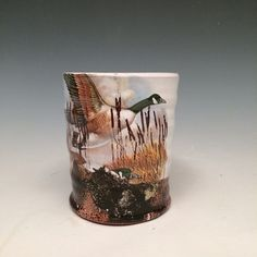 Handmade earthenware mug glazed with a white glaze. It is decorated with Canada goose decals and cattail decals.