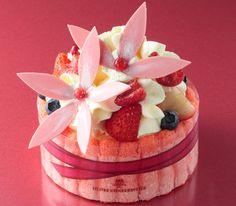 トゥレトゥレトゥレ・ボン  フランス語の「Très Bon!」(=とても素敵)から発想し、大切な人への贈りものが素敵になることを願いTrès Très Très Bon(=とても、とても、とても素敵)というネーミングに。淡い桃色のチョコレートで作った大きな花とベリー類のフルーツで、贈りものに使われるフラワーボックスに見立てたホールケーキです。 ♥ Dessert