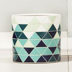 Shop rudi blue planter.   Sleek cylinder gains visual interest in triangular shades of blue, green and white.  Reminds us of vintage ceramic tile but is actually crafted from earthenware.