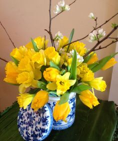 Nothing says spring like tulips. Here, I used 10 yellow ones, plus a few bunches of daffodils. For a color contrast, I arranged them in a blue and white Asian-style vessel and added a branch of quince to tie in the white.