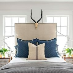 Problem #5 & Solution - Guest bedroom: With no obvious place to put a bed, Laughlin opted for symmetry and centered an extra-tall upholstered bed between two windows.