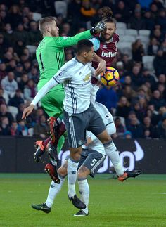 Andy Carroll of West Ham United in action with David De Gea of Manchester United during the Premier League match between West Ham United and...