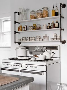 Adding extra shelves over the stove (these were made from pipes and plywood) is a smart use of space in the kitchen.
