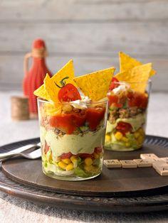 Bunter Salat geschichtet mit Guacamole, Salsa, Hackfleisch und Nachos