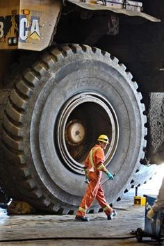 Tar Sands Art: Photograph about Alberta, Canada tar sands mining. A shop mechanic walks past one of the huge tires on a Caterpillar dump truck used in the open-pit tar sands mines to haul tar sands for processing.