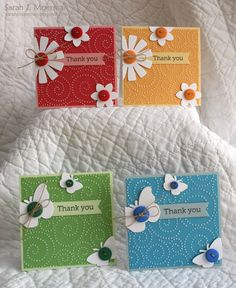Create these cards to use one at a time, or present the group of them as a gift.  The flowers and butterflies are attached with twine or thread and placed onto bright colors that were embossed with swirling dots.  Enjoy these handmade Thank You notes!