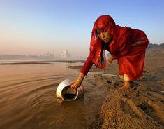 A woman collecting dirty water with the Taj Mahal in the background, highlighting the differences in life