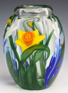 STEVEN LUNDBERG ART GLASS DAFFODIL VASE. PAPERWEIGHT STYLE VASE WITH SEVERAL BLUE AND WHITE FLOWERS AS WELL AS ONE LARGE DAFFODIL. CIRCA 2005