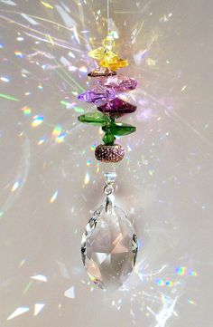 This suncatcher is a lovely blend of 10mm and 14mm Swarovski Heart Crystals in Jonquil, Lt. Topaz, Antique Pink, Violet, Lt. Amethyst and Lilac Shadow. Topping this Purple stem is a 5mm Swarovski Bicone Crystal in Jonquil and the base of the flower stem features 14mm Pure Leaf Pendant Crystals in Fern Green and Peridot.  Reflecting the Purples and Yellows I've accented with a sparkling Multi-acrylic Pave Roundelle.    The Crystals and Pave Bead adorn an exquisite 38mm Swarovski Strass…