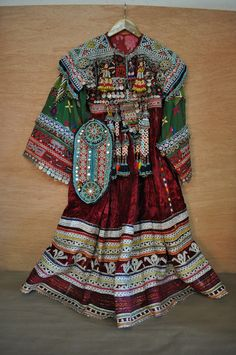 Nomad Afghani Wedding Dress The traditional Nomad Afghani Dress is a staple of the Nomad wardrobe. Women would own two or three of these dresses and wear them everyday. This particular dress is heavily embellished with coins, beads, and tassels. It makes a beautiful sound when the dress is moved. This dress was most likely made for a bride for her wedding day. Each piece has been meticulously hand woven and embellished. The detail on this dress is amazing.