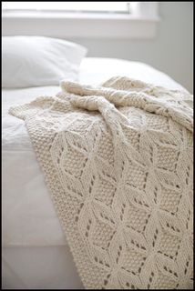 A luxuriously textured wool throw, worked in super-bulky yarn. A smooth, round yarn is recommended for best results with stitch definition. The fabrics motif is created through the use of lace, cables and knit-purl patterning.