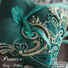 The Teal Prentice Ring Pillow from Luxurious Wedding Accessories has exquisite bead work on luxurious Teal silk fabric. A Teal satin ribbon drapes from the center for the rings.