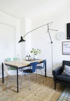 Small space dining area with plank table and vintage restored Arne Jacobsen chairs in the original colours.