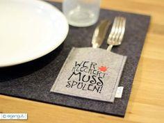 Tischset aus reinem Wollfilz mit aufgesetzter Tasche für Serviette und Besteck. Die Tasche ist bestickt mit dem Motiv *WER KLECKERT MUSS SPÜLEN*.  Die *Grundfarbe des Tischsets gibt es in grau...