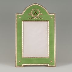 An important Fabergé gilded silver and guilloché enamel , workmaster Anders Nevalainen, ST Petersburg, circa 1904-1908, rectangular form with raised central arch, enameled in translucent lime green over a wavy engine-turned ground, centering a rectangular aperture within a ribbon-tied laurel border, surmounted by a gilt Roman numeral 'X' within a ribbon-tied laurel wreath, set with rosettes at the corners, all within a leaf tip border Christie's Geneva,