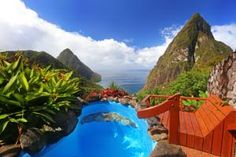 Overlooking the World Heritage Piton Mountains and the Caribbean Sea, Ladera Resort's signature open-air suites feature natural stonework, cut tile, hard...