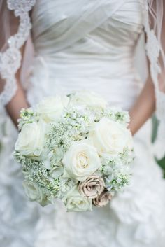 Hand tied bouquet, queen annes lace, white hydrangea, white stock and white roses.