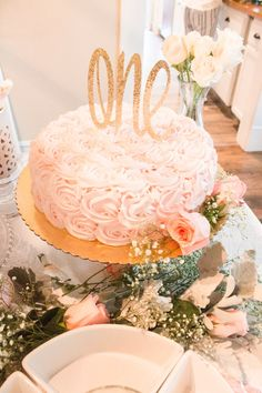 A pink and white floral themed first birthday party with touches of gold glitter and lots of sweets and cake stands designed by Kristyn Cole of At Home With Kristyn Cole for her daughter Karsyn.