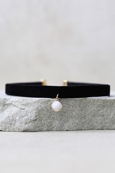 """No need to look any further, the Tranloev The One Black and White Choker Necklace is finally here! This stretchy velvet choker has a white marbled stone accent in a shiny gold setting. Necklace measures 10.25"""" long, with a 2"""" extender chain."""
