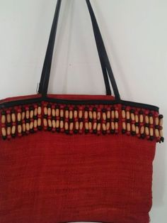 Cole Haan straw woven bag with wooden beads running around the top. It is extremely well made with double reinforced lining. It is a redish oran