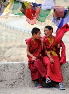 Young Tibetan monks laugh together under Buddhist prayer flags.