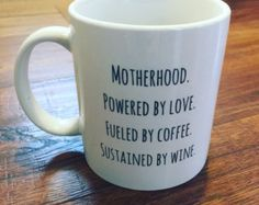 One of our best selling tees; Motherhood. Powered by Love. Fueled by Coffee. Sustained by Wine. is now available on a coffee mug!  These mugs are 11oz standard size coffee mugs. And they are PRINTED, not vinyl! They are dishwasher and microwave safe, the ink will not peel, chip, fade or wash away.  This is a right handed mug, meaning the design will face outward while drinking/holding it in your right hand. If youd like this printed on the opposite side, for a left hand mug, please make...
