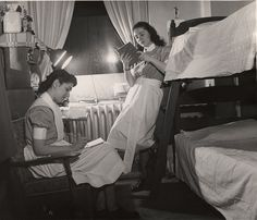 Two young 1940s nursing students studying by lamplight well into the night
